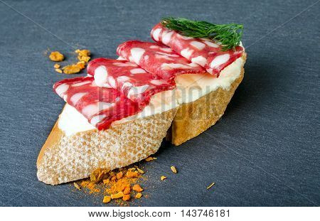 Sandwiches with salami and dill on a dark background.
