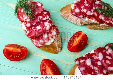 Sandwiches with salami tomato and dill on a blue background.