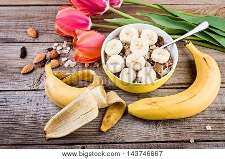 oatmeal with banana and milk for breakfast on rustic wooden table.