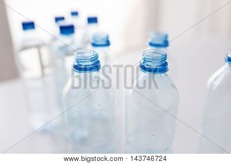 recycling, healthy eating and food storage concept - close up of empty plastic water bottles on table