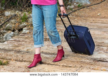 Person walking on old wooden bridge female Legs and Hand casual vacation Clothing red high Heels Shoes and Jeans green Forest and Mountains on background