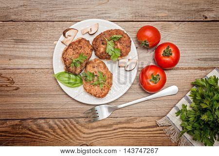 grilled pork cutlets. Fried pork burgers with tomatoes on the wooden background