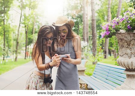 Two girls friends outdoors surprised watching photos at digital camera. Young female tourists in boho chic fashion clothes, having fun in summer park. Travelling together, lifestyle portrait.