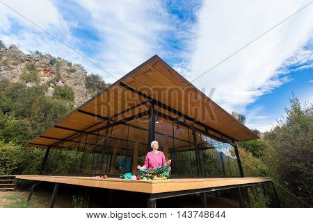 Person doing Yoga Exercise on wooden Terrace of rural Cabin with large Windows Mountains and Sky on Background