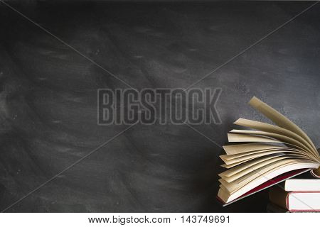 an open book front of a blank black board