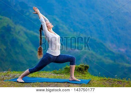 Yoga outdoors - sporty fit woman doing Ashtanga Vinyasa Yoga asana Virabhadrasana 1 Warrior pose posture in HImalayas mountains