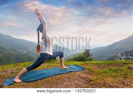 Yoga outdoors - sporty fit woman doing Ashtanga Vinyasa Yoga asana Virabhadrasana 1 Warrior pose posture in HImalayas mountains on sunset