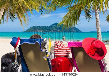 Couple at the beach with their suitcases