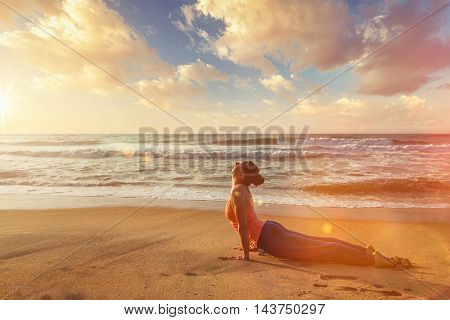 Yoga outdoors on beach - woman practices Ashtanga Vinyasa yoga Surya Namaskar Sun Salutation asana Urdhva Mukha Svanasana - upward facing dog pose on sunset. With light leak and lens flare