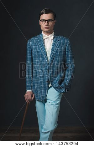 Retro 1920S Fashion Man Wearing Blue Checkered Jacket. Standing With Cane.