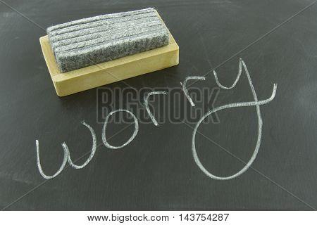 Worry written in white chalk on blackboard with eraser.