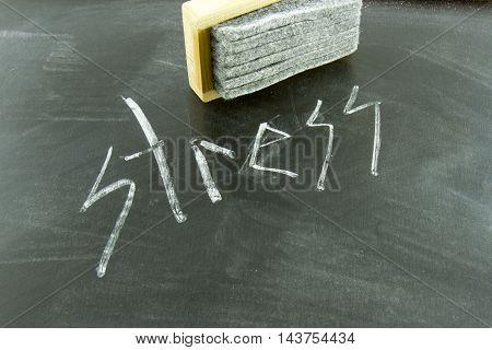 Stress written in white chalk on blackboard with eraser.