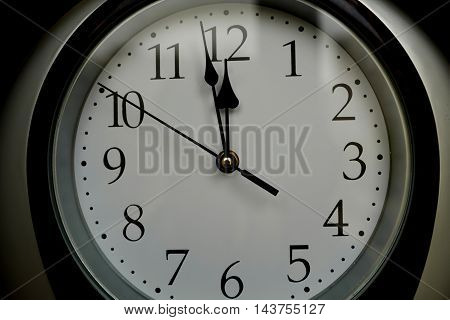 three minutes to twelve - Closeup of hands on wall clock face