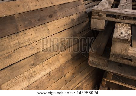 Wall made of dark brown wooden planks surface as background image with vignette.