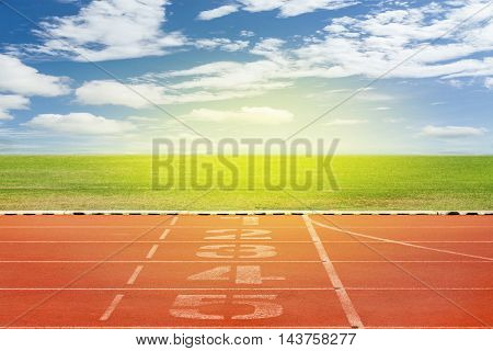 Start and Finish point of race track Running track number in front of tracks in stadium with beautiful green grass with blue sky scenery background