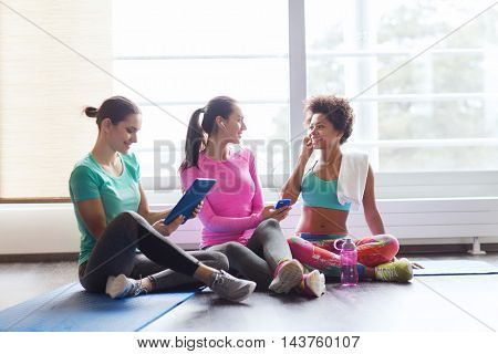 fitness, sport, technology and lifestyle concept - group of happy women with smartphone, earphones and tablet pc computer listening to music in gym