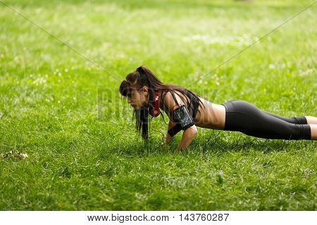Young brunette athletic woman doing push ups on green grass. Image with copy space