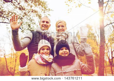family, childhood, season, gesture and people concept - happy family waving hands in autumn park