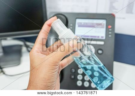 Hold a transparent bottle of alcohol for hygiene with the office background
