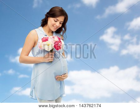 pregnancy, motherhood, holidays, people and expectation concept - happy pregnant woman with flowers touching her big belly over blue sky and clouds background