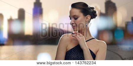beauty, jewelry, people and luxury concept - beautiful young asian woman with earring over city silhouette and lights background