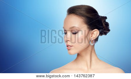 beauty, jewelry, accessories, people and luxury concept - close up of beautiful asian woman face with earring over blue background