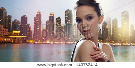 beauty, jewelry, people and luxury concept - beautiful young asian woman with earring over dubai city night lights background
