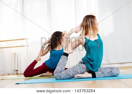 Closeup portrait of two slim young women practicing pigeon pose in fitness class
