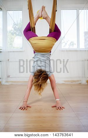 Young woman practicing fly yoga exercises indoor, antigravity yoga in studio