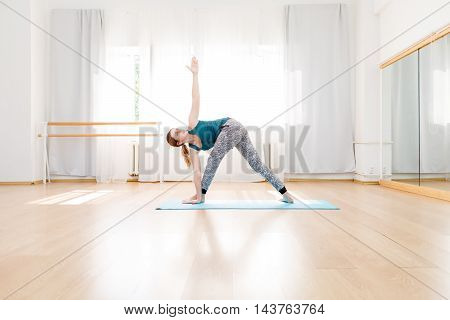 Young flexible blonde woman in utthita trikonasana triangle pose in yoga center