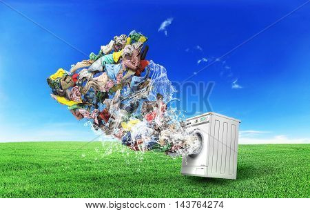 Clothing concept. Tornado of clothes flies from washing machine at nature background. Concept of Big washing.