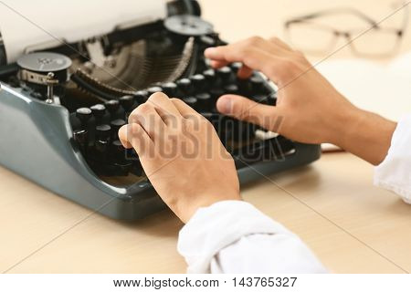 Man working on retro typewriter at desk