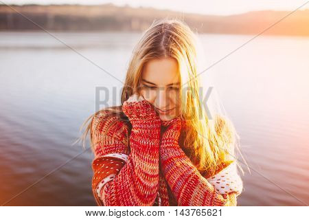 Adorable shy young girl wearing warm clothes standing and smiling by a lake. Sun light at sunset.