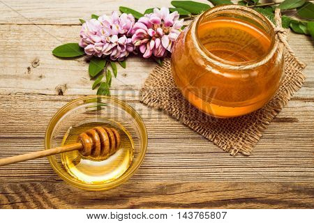 Acacia honey and fliwers on wooden background. Selective focus.