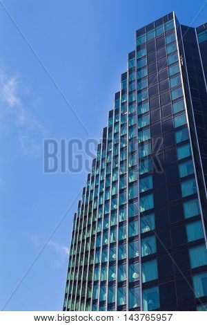 Detail of a modern skyscraper which is reflecting the bright blue summer sky. Downtown Detroit Michigan USA