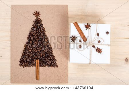 Christmas tree made from coffee beans and gift box on the wooden background. Top view copy space.Winter holidays concept.