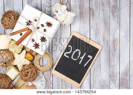 Christmas decoration and gift box over the wooden background. Winter holidays concept. 2017 on the tablet.Space for text.