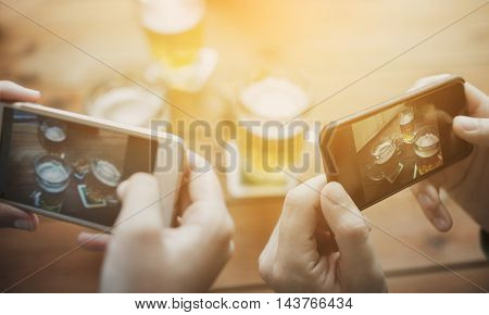 people and technology concept - close up of hands with smartphone picturing beer at bar