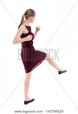 skinny woman funny fights waving his arms and legs. Isolated over white background. A girl in a burgundy dress has foot.