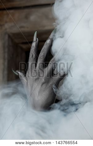 Black hands of the devil on background of a smoke