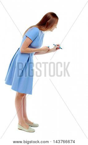 back view of writing beautiful woman. Rear view people collection.  backside view of person. Isolated over white background. Skinny girl in a blue dress draws a felt-tip pen. side view