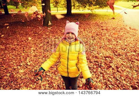 autumn, childhood, nature and people concept - happy little girl playing with fallen leaves in park