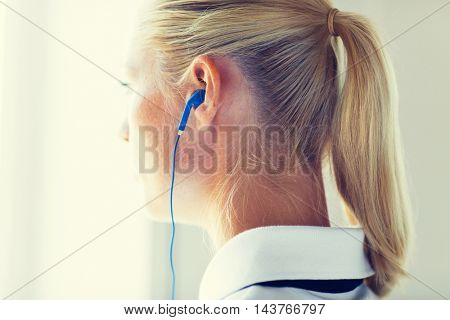 technology, music and people concept - close up of woman in earphones at home
