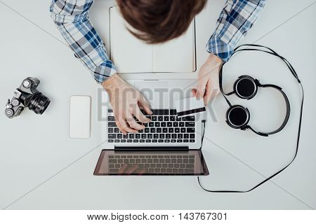Shopping online. Close-up top view of man working on laptop and holding credit card