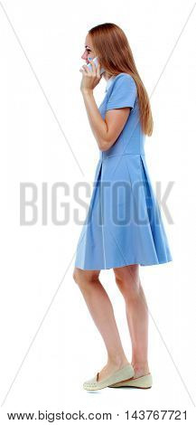 side view of a woman walking with a mobile phone. beautiful girl in motion.  backside view of person.  Rear view people collection. Isolated over white background. blonde in blue dress talking on the