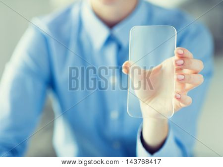 business, technology and people concept - close up of woman hand holding and showing transparent smartphone at office