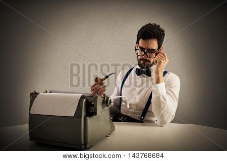 Man with glasses and pipe write with a typewriter