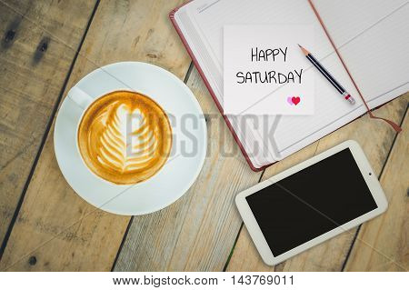 Happy Saturday on paper with coffee cup on wood background