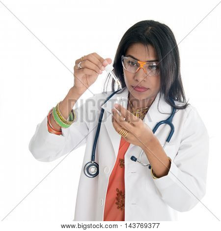 An Indian female medical or scientific researcher or woman doctor looking at a test tube of clear solution in a laboratory.