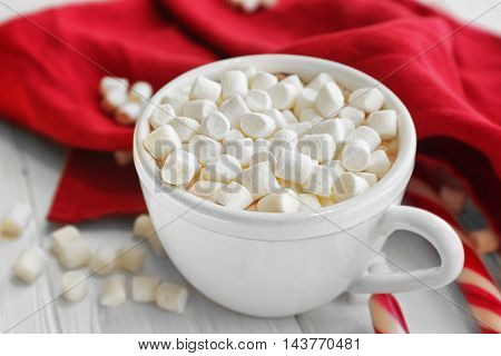 Cup of hot chocolate with marshmallows and candy, closeup